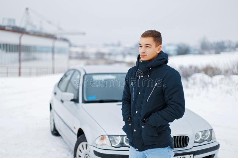 Young man in winter clothes standing near the car. A young man in winter clothes stands next to a gray car royalty free stock photography