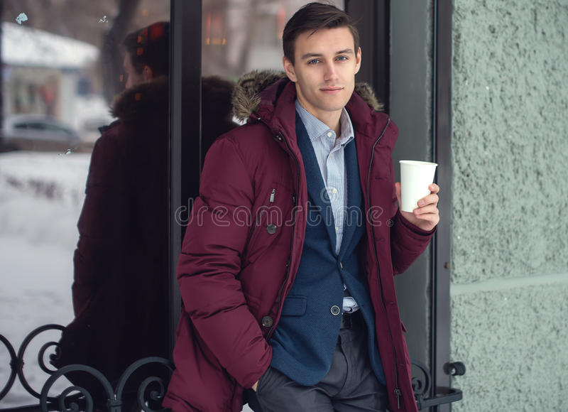 Young man in winter coat woth coffee to go. Standing against the cafe wall stock photos