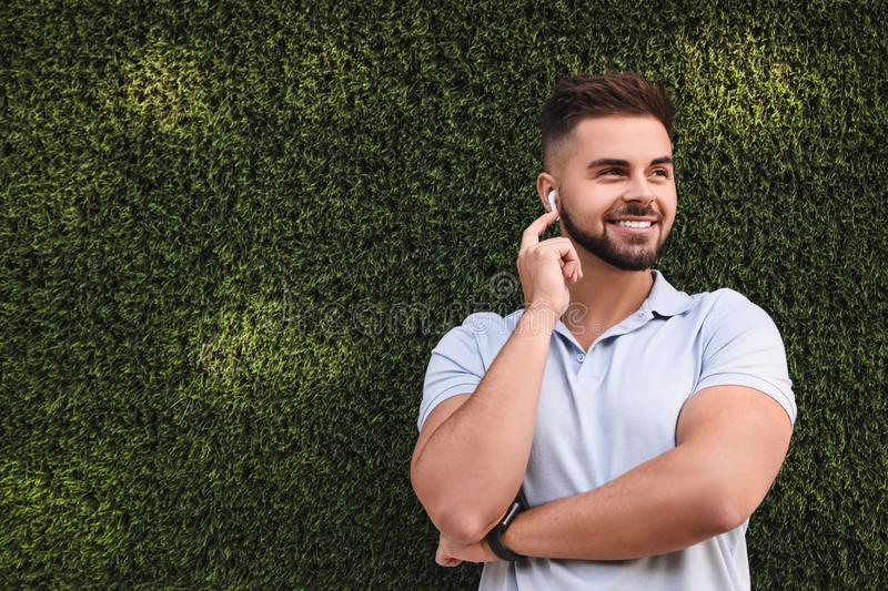 Young man with wireless headphones listening to music near green grass wall stock images