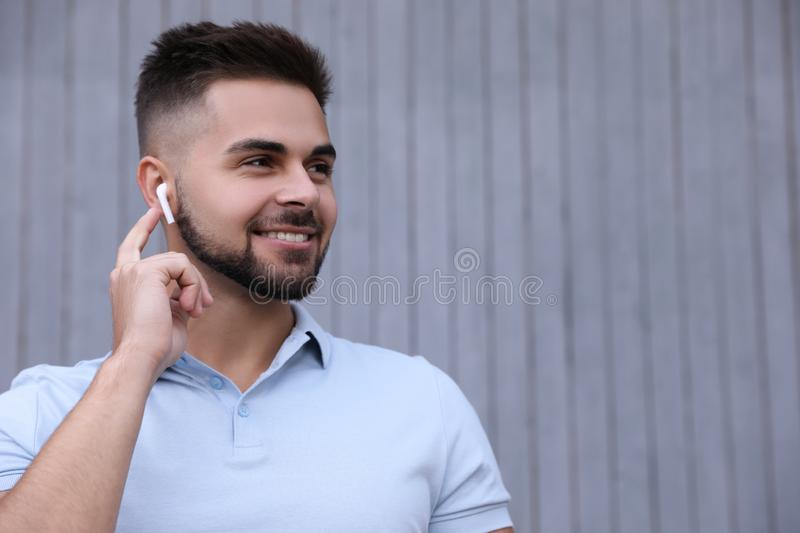 Young man with wireless headphones listening to music near wall. Space for text royalty free stock image