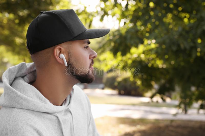 Young man with wireless headphones listening to music in park stock images