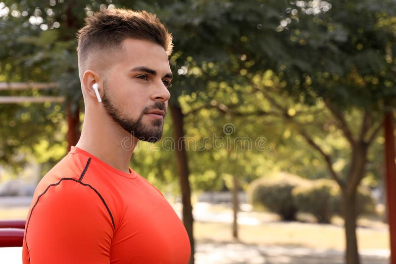 Young man with wireless headphones listening to music on sports ground royalty free stock photos