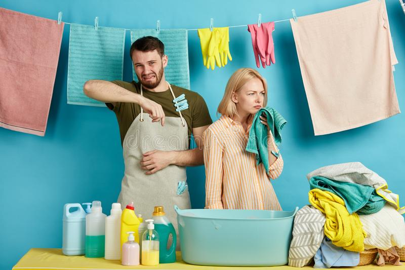 Young man and woman in aprons are allergic to washing powder, soap royalty free stock photography