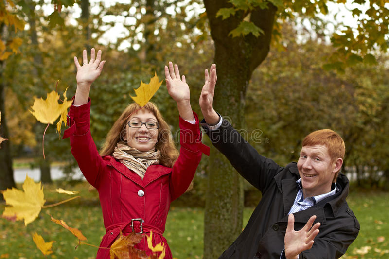Young man and woman in the autumn park. Young men and women in the autumn park catch the falling yellow autumn leaves. They laugh, enjoy life, reach for leaves stock photos