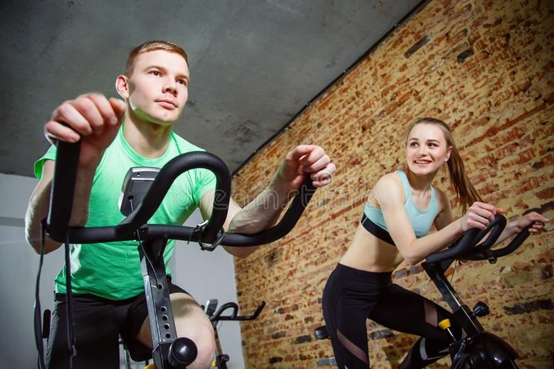 Young man and woman biking in the gym, exercising legs doing cardio workout cycling bikes. royalty free stock image