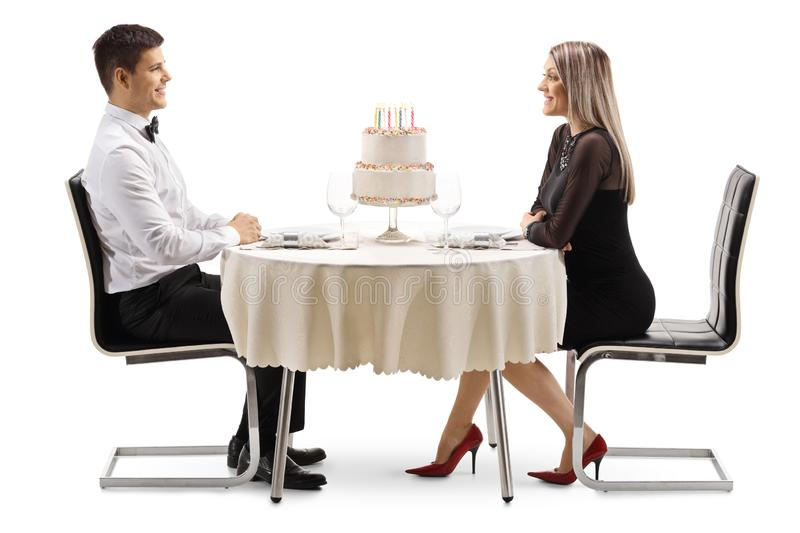 Young man and woman celebrating a birthday at a restaurtant with a cake on a table royalty free stock image