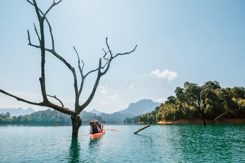 Young man and woman couple explorers travelers exploring the Cheow Lan lake in Thailand using a canoe royalty free stock images