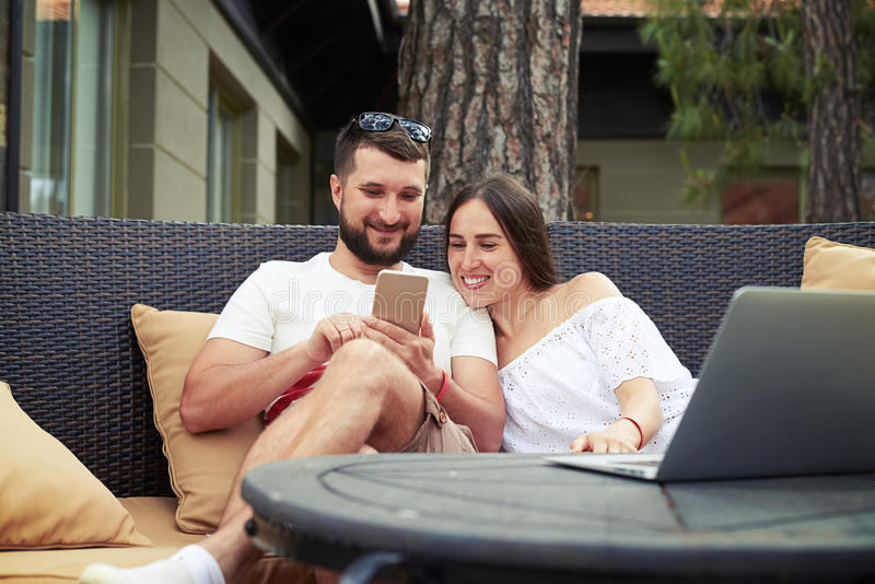 Young man and woman on cozy couch are watching something on the stock photos