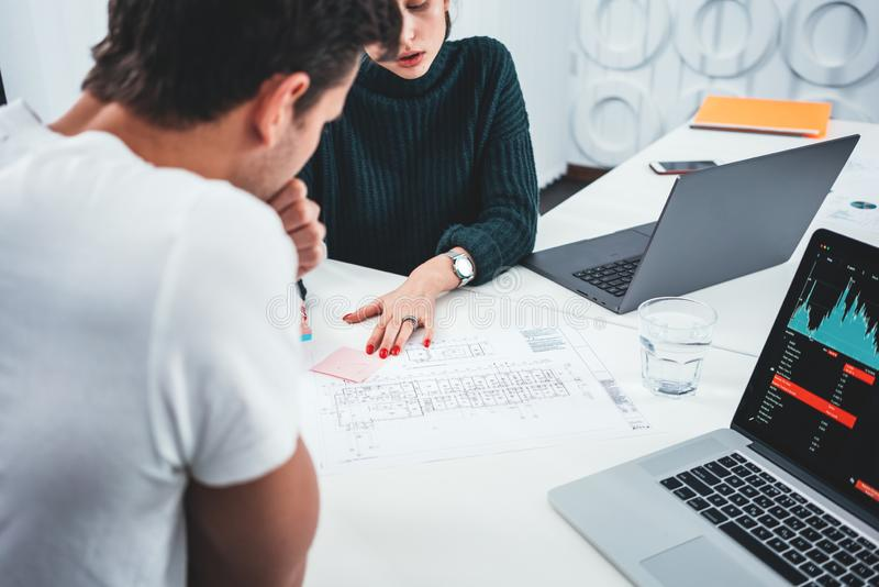 Young man and woman designer sketching a construction project at laptop and drawing plan while working at office stock image