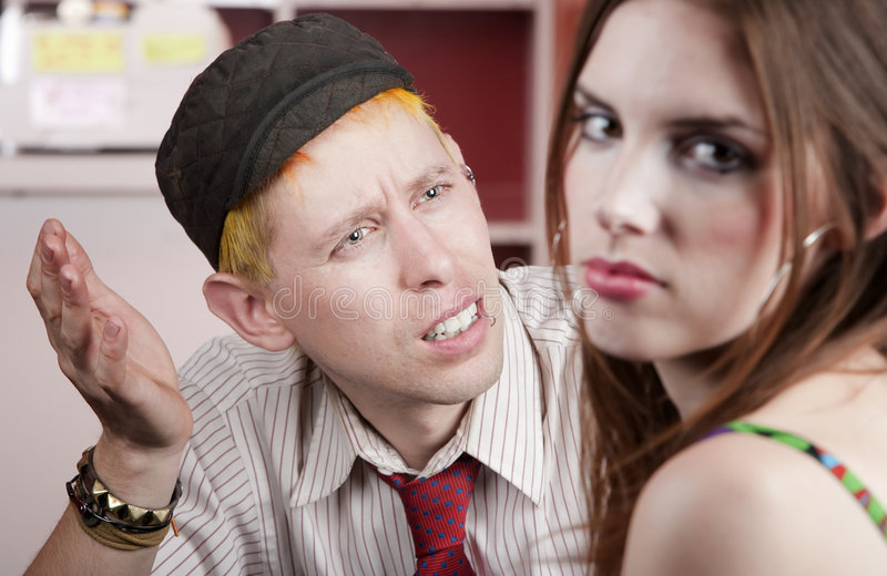 Young man and woman with a disagreement. Young man confused by disagreement with pretty woman stock images