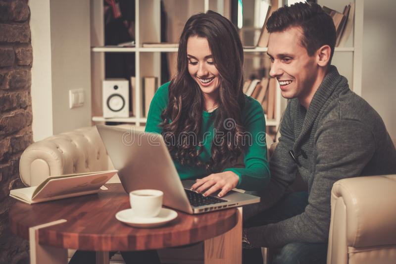 Young man and woman discussing something. Young couple with laptop and coffee behind table stock photo