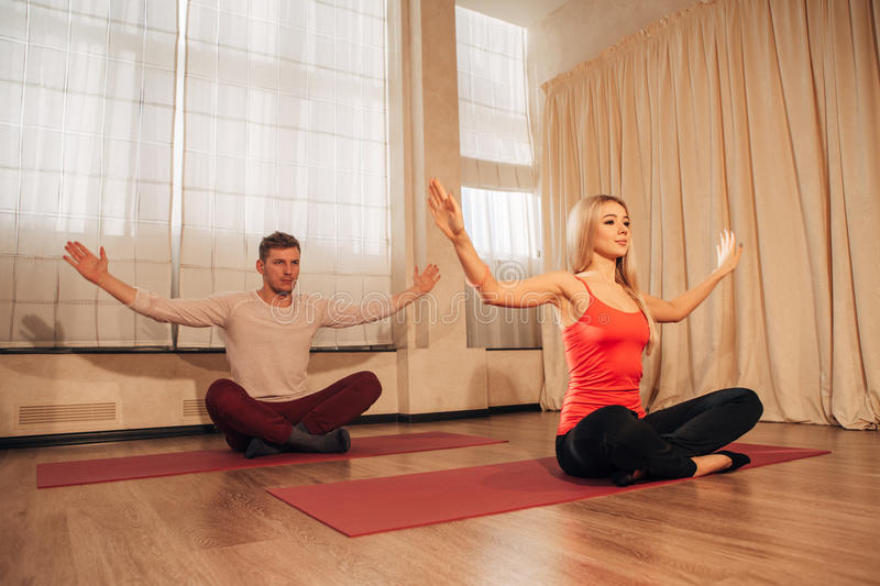 Young man and woman doing yoga exercises royalty free stock photo