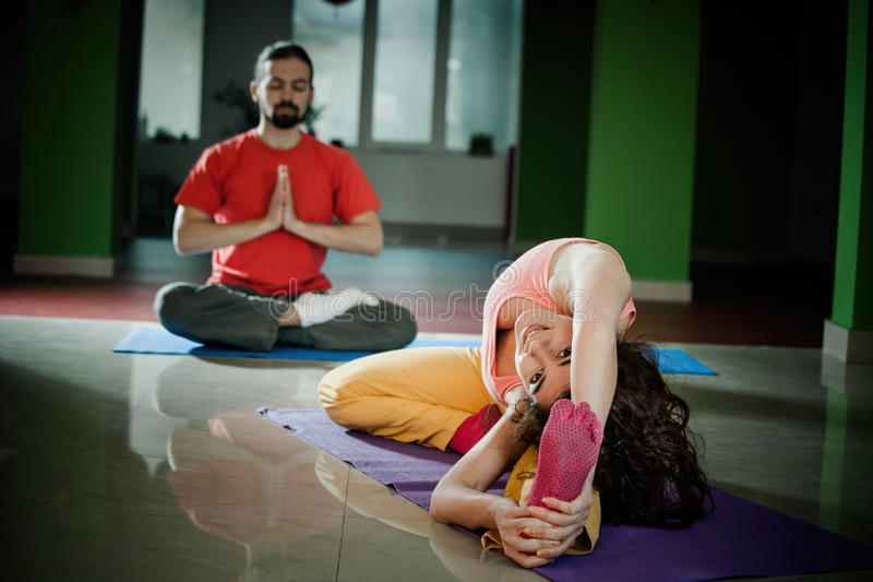 Young man and woman doing yoga indoor. Young men and women doing yoga indoor healthy lifestyle concept royalty free stock images