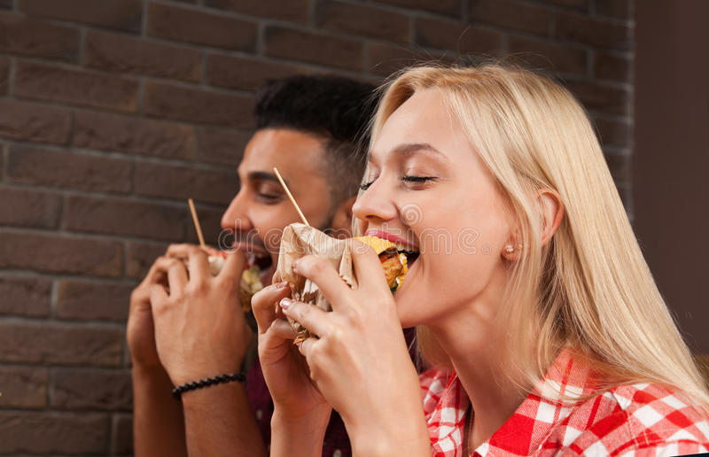 Young Man And Woman Eating Fast Food Burgers Sitting At Wooden Table In Cafe. Friends Meeting Communication royalty free stock photography