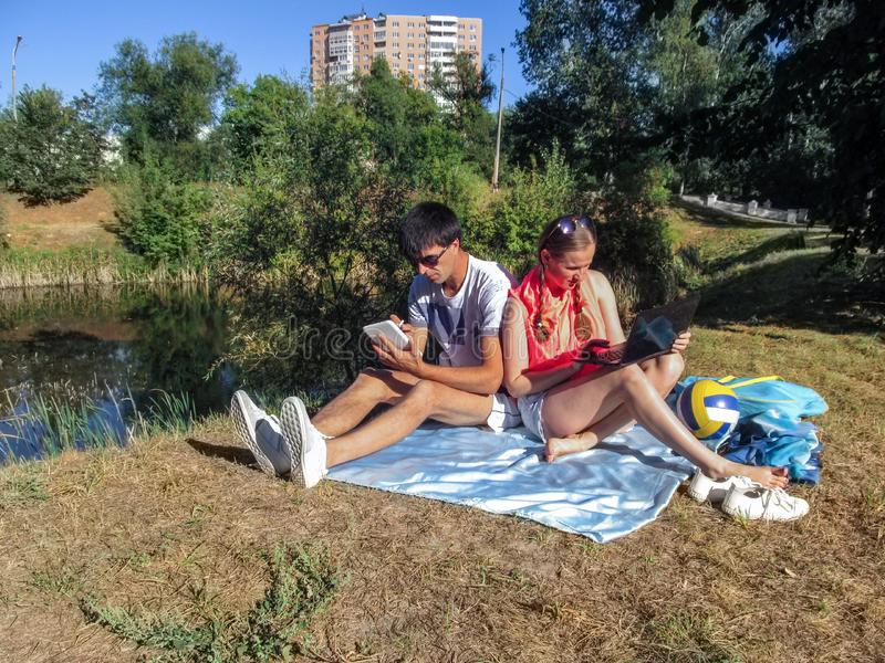Young man and woman with gadgets while relaxing outdoors. The concept of Internet addiction, love couple  on a date use a laptop royalty free stock photos