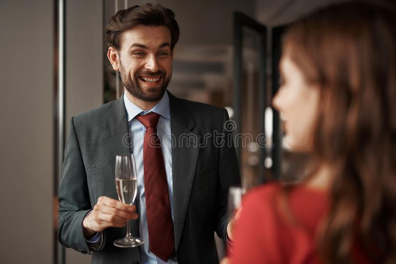Young man and woman have romantic meeting. Concept of romantic date and celebration. Waist up portrait of happy gentleman with champagne glass looking at young royalty free stock images