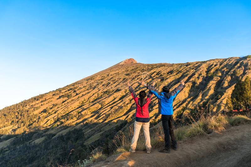 Young man and woman hiker spreading hand, enjoy and happy with mountain top view. royalty free stock photos