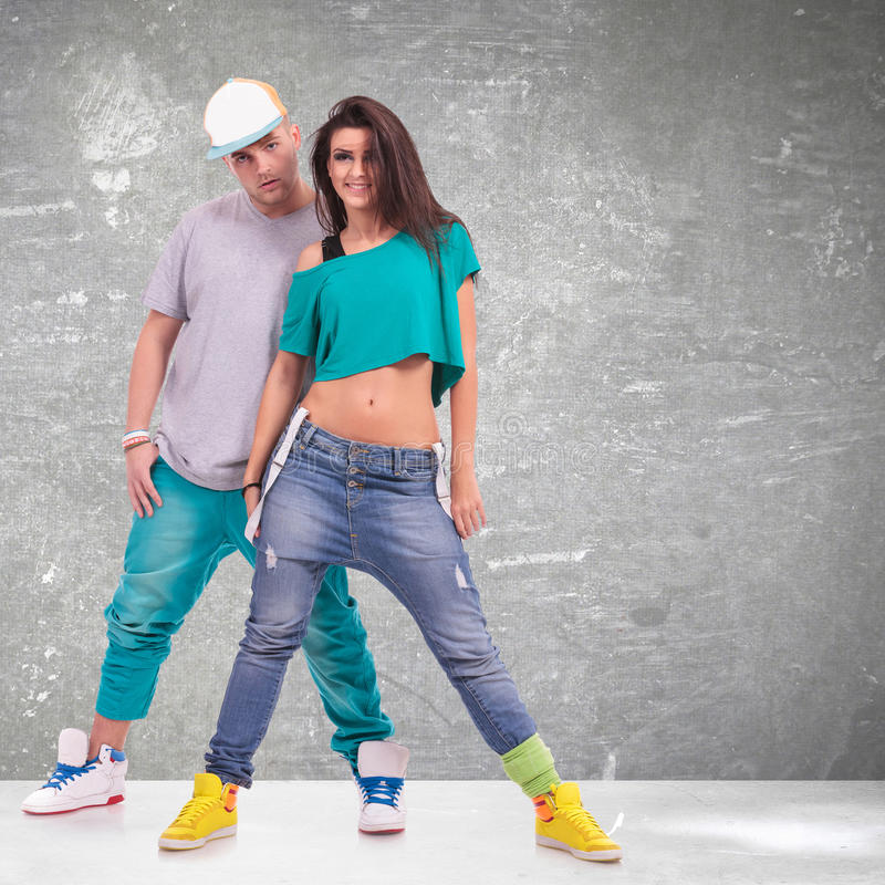 Young man and woman hip-hop dancers. Couple of young men and women hip-hop dancers, posing at studio royalty free stock image