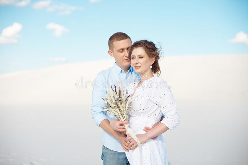 Young man and woman hugging on a background of white sand, dunes. Love story in the void. royalty free stock image