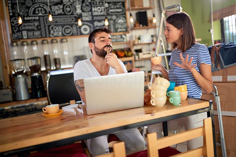 Young man and woman with laptop ready to open their cafe.Small business owner stock photography
