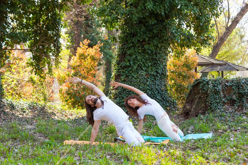 Young man and woman practice yoga outdoor in wood beautiful summer day royalty free stock images