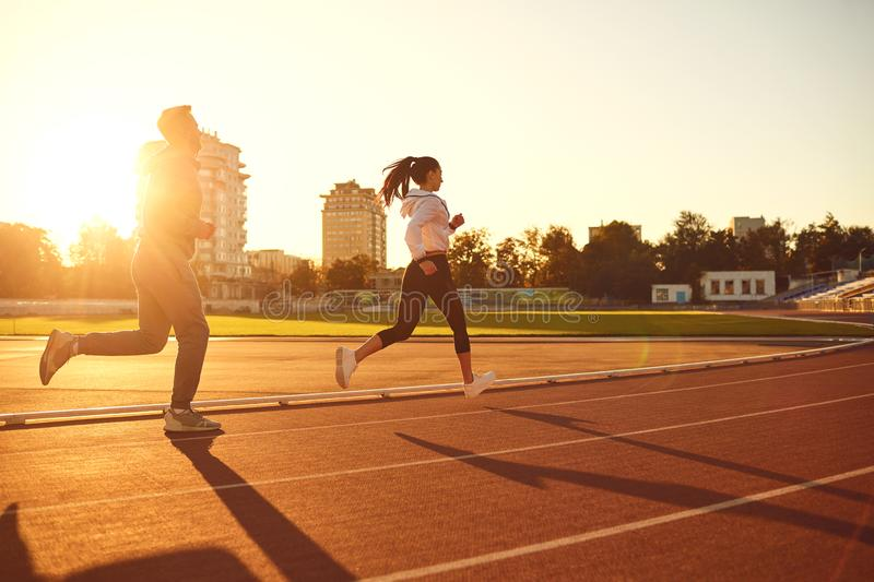 Young man and woman runners run in the morning at dawn. Young men and women runners run in the morning at dawn.Jogging. Health. Healthy lifestyle stock image