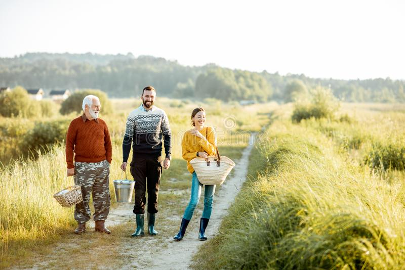 Young man and woman with senior grandfather walking outdoors stock image