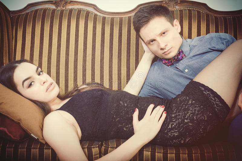 Young man and woman In edition looking seductively at camer. Retro vintage couple lying on the retro furniture. Young men and women In edition looking stock image