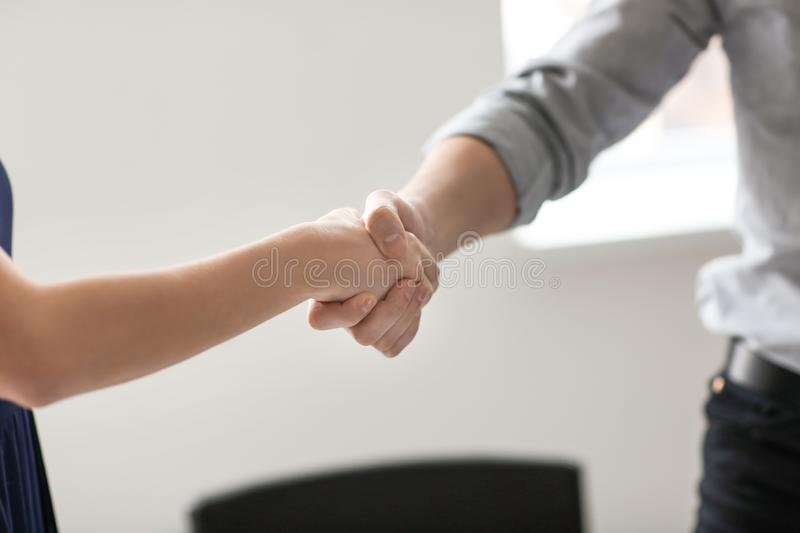 Young man and woman shaking hands at business meeting stock photos