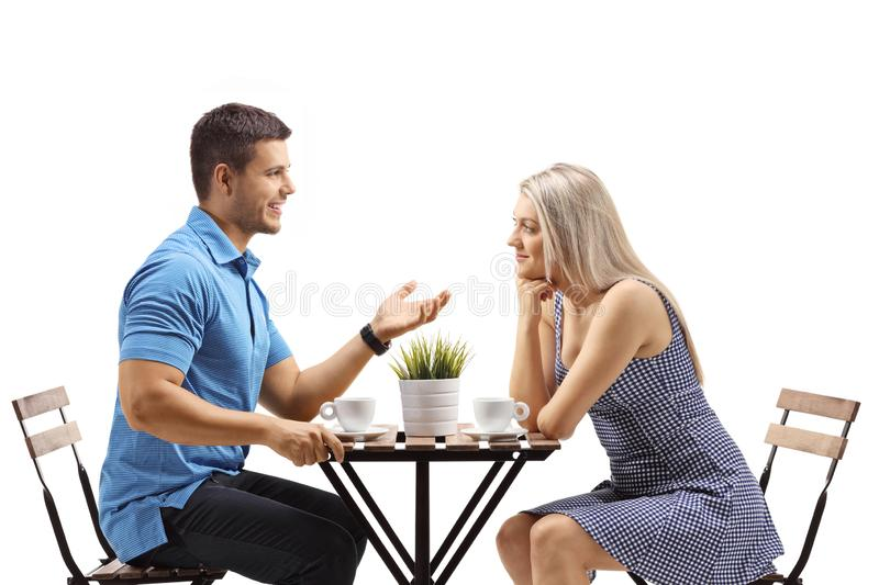 Young man and woman sitting at a coffee having a conversation stock photos