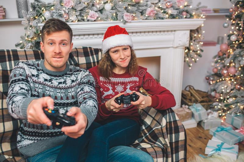 Young man and woman sitting and playing games together. They push buttons on console. People worry. They play in stock image