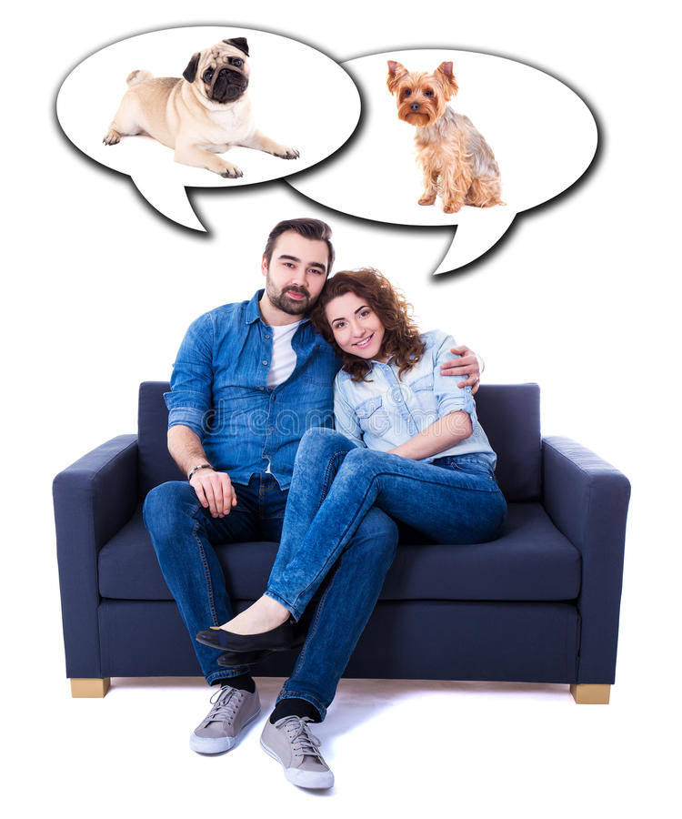 young man and woman sitting on sofa and dreaming about dogs isolated on white stock photography