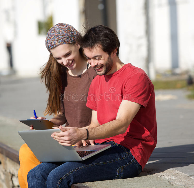 Young man and woman smiling at laptop outdoors. Portrait of a young men and women smiling at laptop outdoors royalty free stock photos