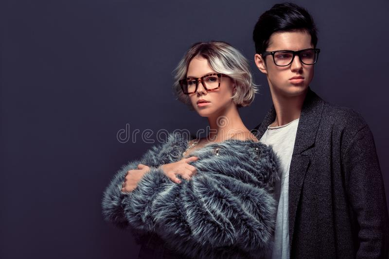 Young man and woman studio shoot isolated on grey wall fashion professional royalty free stock photography