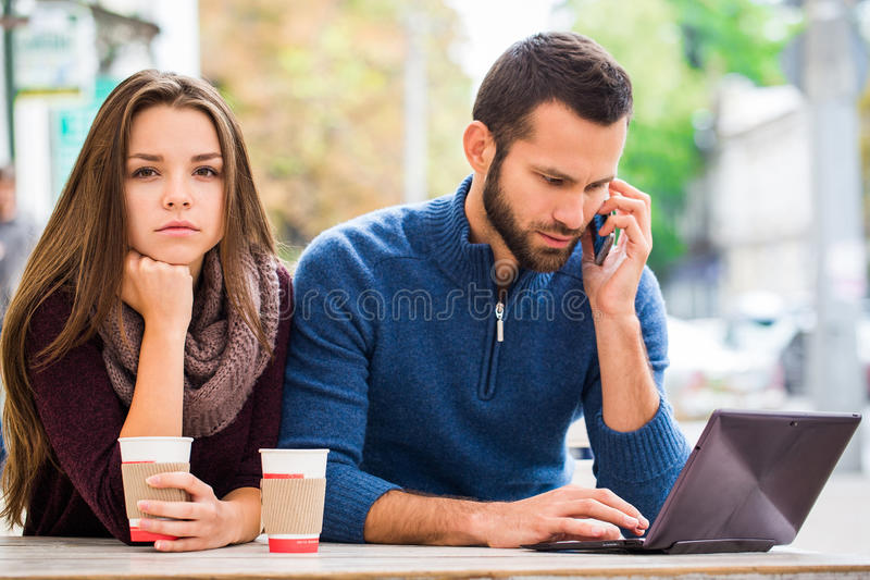 Young man and woman talking , they have fun , they have in their hands the tablet . They drink coffee or tea. laptop royalty free stock photo
