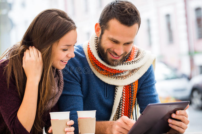 Young man and woman talking , they have fun , they have in their hands the tablet . They drink coffee or tea. stock photos