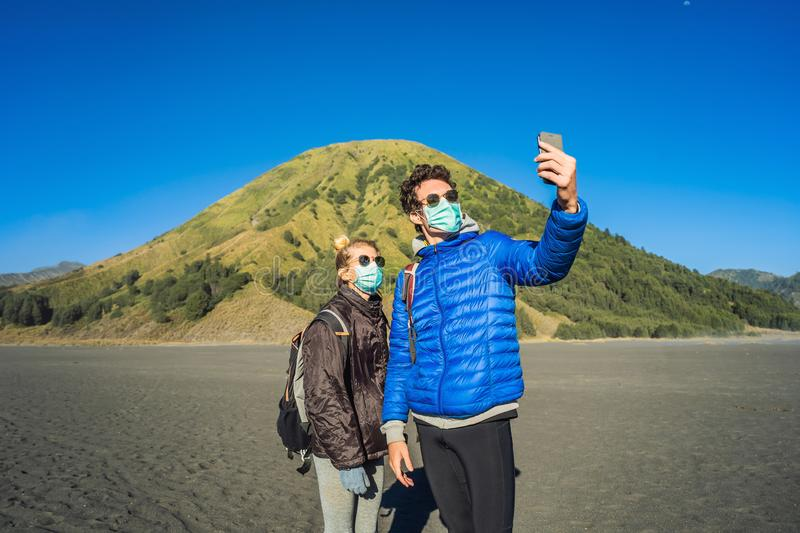 Young man and woman tourists make a selfie in the Bromo Tengger Semeru National Park on the Java Island, Indonesia. They. Young men and women tourists make a royalty free stock images
