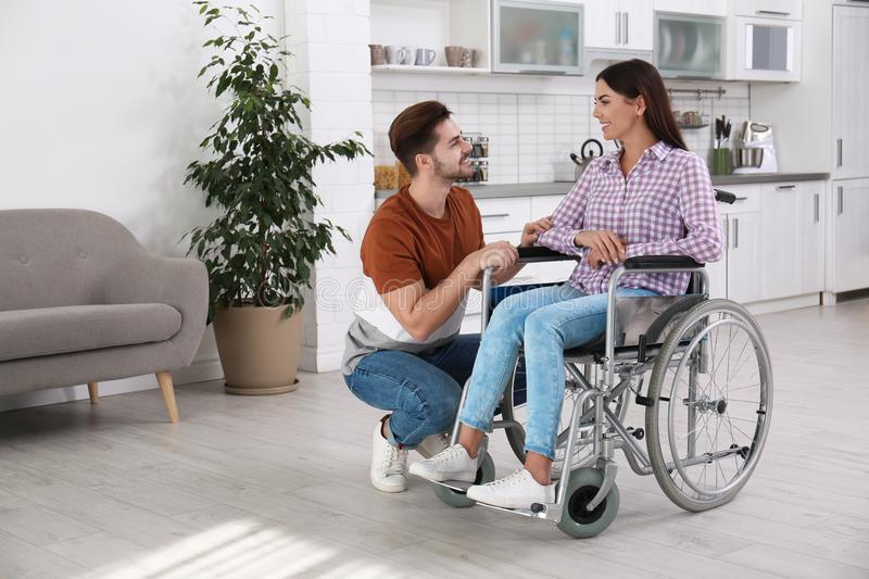 Young man with woman in wheelchair stock photography
