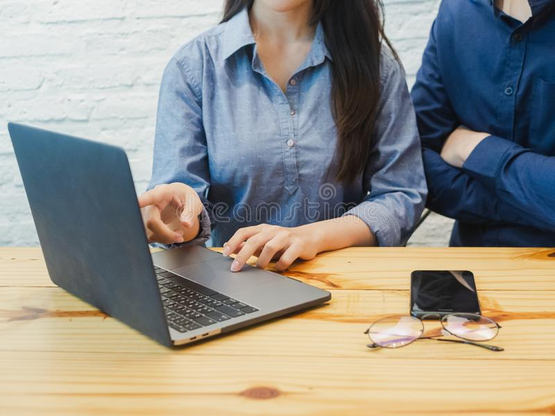 Young man and woman working in the office. Business woman pointing at the labtop. Coworking, Teamwork, Business partner Concept royalty free stock photography
