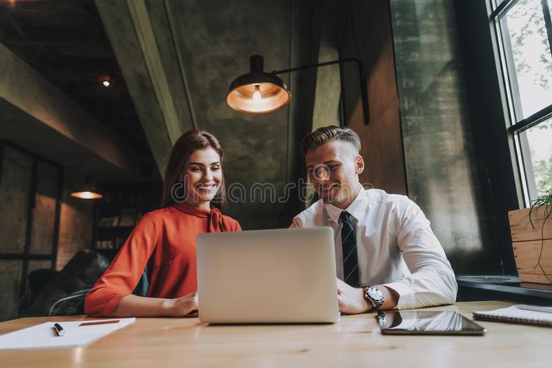 Young man and woman working together in office stock photography