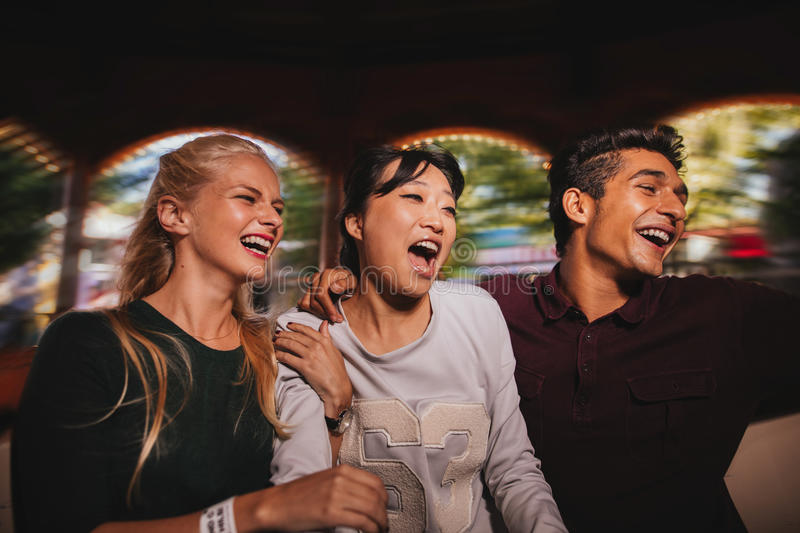 Young man and women having fun together on amusement park. Group of friends on amusement park ride. Young men and women having fun together royalty free stock photos