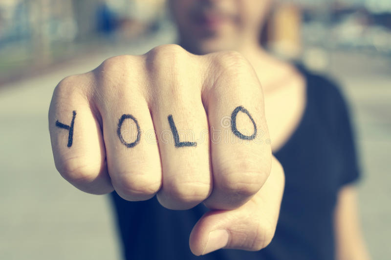 Young man with the word yolo, for you only live once, tattooed i royalty free stock image