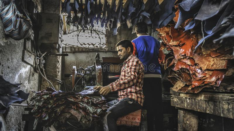 Young man work hard in the leather factory inside the dharavi slum in mumbay royalty free stock photography