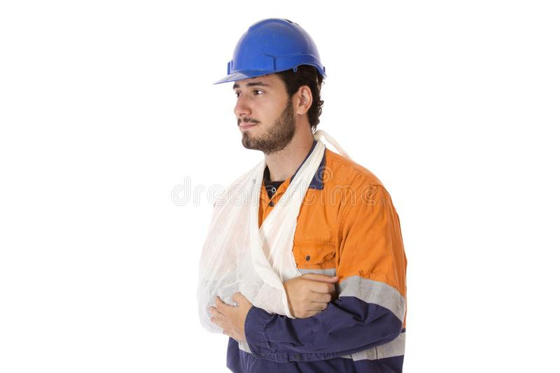 Workers Compensation Injury. A young man in work uniform wearing a sling facing to the side royalty free stock image