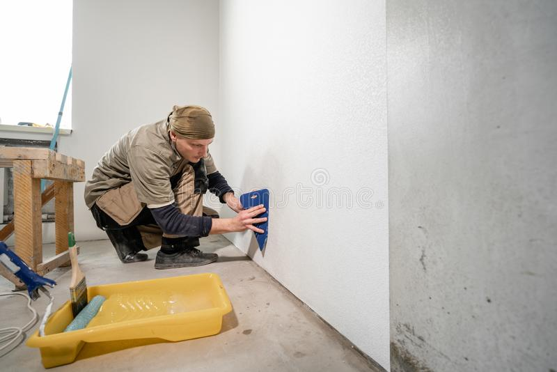 Young man, worker glueing wallpapers on concrete wall. Repair the apartment. Home renovation concept. White Wallpaper royalty free stock images