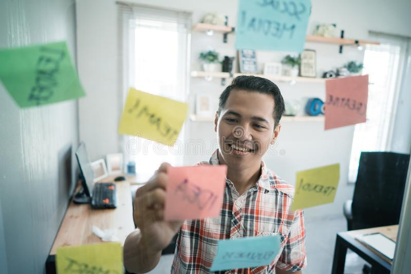 Young man worker write paper notes on the glass wall. In the office room royalty free stock photography