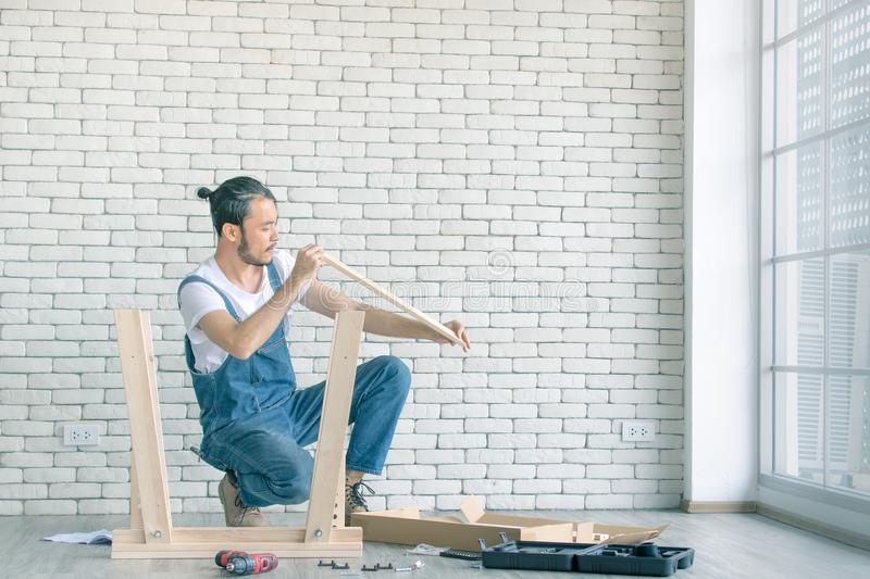 Young man working as handyman, assembling wood table with equipments, concept for home diy and self service.in the office there i stock image