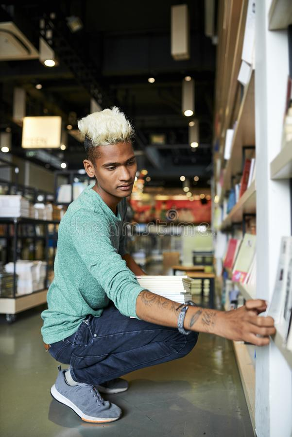 Young man working in bookstore. Serious handsome hipster young black man with blond Mohawk crouching on floor and putting books on shelves while working in royalty free stock photo