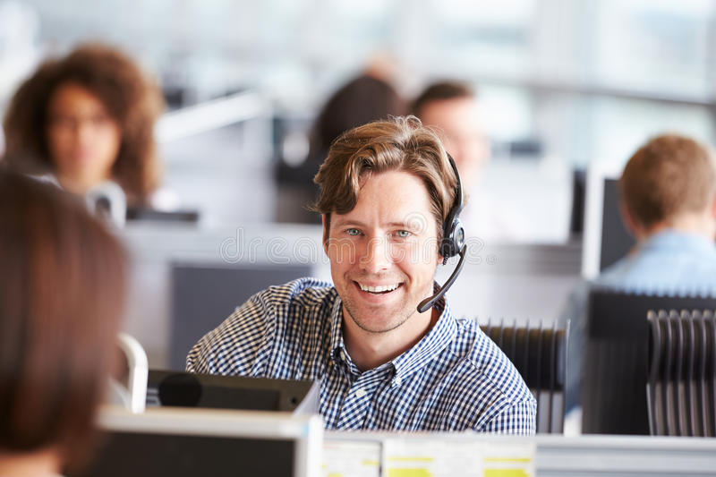 Young man working in call centre, looking to camera. Young men working in call centre, looking to camera stock image