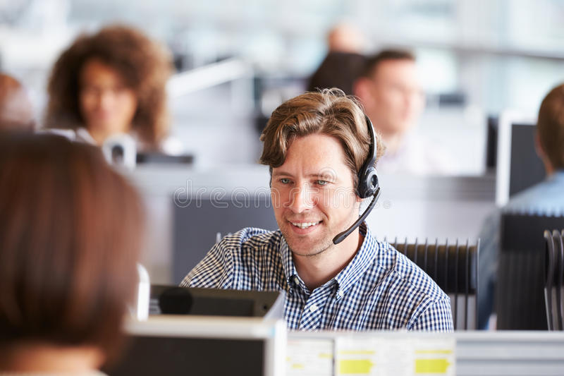 Young man working in call centre, surrounded by colleagues. Young men working in call centre, surrounded by colleagues royalty free stock image